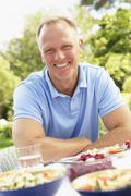 Man Enjoying Meal In Garden - stock photo