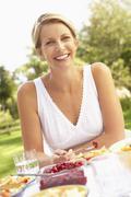 Woman Enjoying Meal In Garden - stock photo