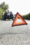Couple Broken Down On Country Road With Hazard Warning Sign In Foreground - stock photo
