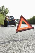 Mother And Daughter Broken Down On Country Road With Hazard Warning Sign In Stock Photos