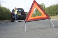 Stock Photo of Female Driver Broken Down On Country Road With Hazard Warning Sign In Foreground