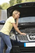Female Driver Broken Down On Country Road - stock photo