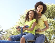Mother And Daughter Riding On Seesaw In Park Stock Photos