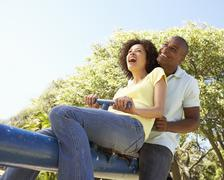 Portrait Of Young Couple Riding On SeeSaw In Park Stock Photos