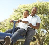 Father and Son Riding On SeeSaw In Park Stock Photos