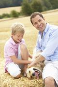 Father And Son Sitting With Dog On Straw Bales In Harvested Field Stock Photos
