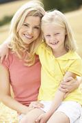 Mother And Daughter Sitting On Straw Bales In Harvested Field Stock Photos