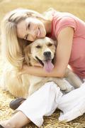 Woman Sitting With Dog On Straw Bales In Harvested Field Stock Photos