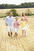 Family Running Together Through Summer Harvested Field Stock Photos
