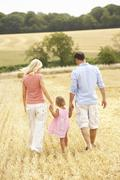 Family Walking Together Through Summer Harvested Field Stock Photos