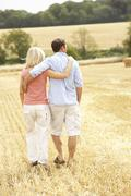 Couple Walking Together Through Summer Harvested Field - stock photo