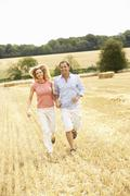 Couple Running Together Through Summer Harvested Field - stock photo