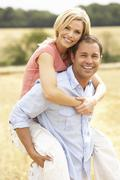 Couple Having Piggyback In Summer Harvested Field Stock Photos