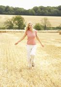 Woman Running Through Summer Harvested Field Kuvituskuvat