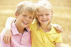 Portrait Of Boy And Girl In Summer Harvested Field Stock Photos