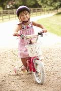 Girl Learning To Ride Bike Wearing Safety Helmet - stock photo