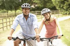 Couple Cycling In Countryside Wearing Safety Helmets Stock Photos