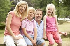 Muotokuva perhe istuu aidan maaseudulla Kuvituskuvat