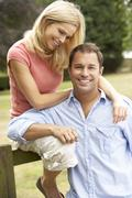 Couple Relaxing In Countryside Sitting On Fence - stock photo