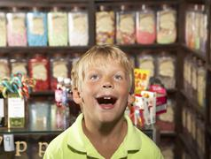Excited Boy Standing In Sweet Shop - stock photo