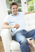 Man Sitting On Sofa Relaxing At Home - stock photo