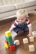 Young Boy Playing With Coloured Blocks At Home - stock photo