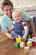 Father And Son Playing With Coloured Blocks At Home Stock Photos