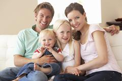 Family Sitting On Sofa At Home Together Stock Photos