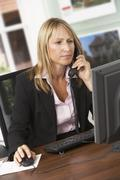 Female Estate Agent Talking On Phone At Desk Stock Photos