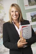 Portrait Of Female Estate Agent In Office Stock Photos
