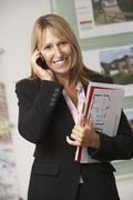 Portrait Of Female Estate Agent In Office On Phone Stock Photos