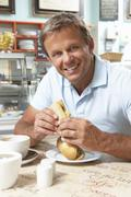 Stock Photo of Male Customer Enjoying Sandwich And Coffee In Café