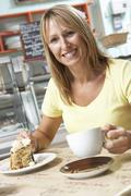 Female Customer Enjoying Slice Of Cake And Coffee In Café Stock Photos