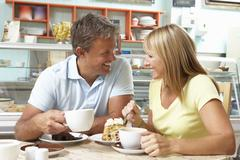 Couple Enjoying Slice Of Cake And Coffee In Café Stock Photos