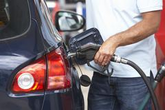 Detail Of Male Motorist Filling Car With Diesel At Petrol Station - stock photo