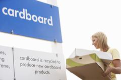 Stock Photo of Woman At Recycling Centre Disposing Of Cardboard