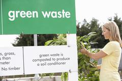 Man At Recycling Centre Disposing Of Garden Waste - stock photo