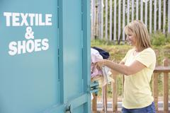 Woman At Recycling Centre Disposing Of Clothing Stock Photos