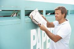 Man At Recycling Centre Disposing Of Old Newspapers Stock Photos