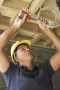 Electrician Working On Wiring In New Home Stock Photos