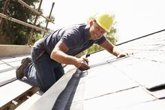 Roofer Working On Exterior Of New Home - stock photo