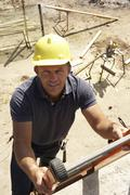 Construction Worker Climbing Ladder On Building Site For New Home - stock photo