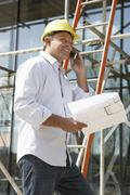 Architect With Plans Outside New Home Talking On Mobile Phone Stock Photos