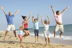 Portrait Of Three Generation Family On Beach Holiday Jumping In Air Stock Photos