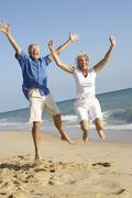 Senior Couple Enjoying Beach Holiday Jumping In Air Stock Photos