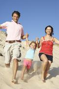 Stock Photo of Family Enjoying Beach Holiday Running Down Dune