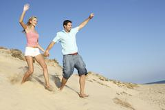 Couple Enjoying Beach Holiday Running Down Dune Stock Photos