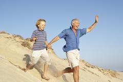 Grandfather And Grandson Enjoying Beach Holiday Running Down Dune Stock Photos