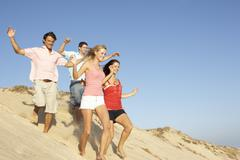 Group Of Friends Enjoying Beach Holiday Running Down Dunes - stock photo