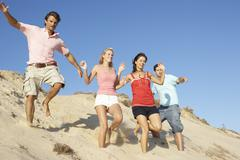 Group Of Friends Enjoying Beach Holiday Running Down Dunes Stock Photos